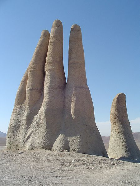 A sculpture of a giant hand reaches for the stars in the middle of the Atacama desert